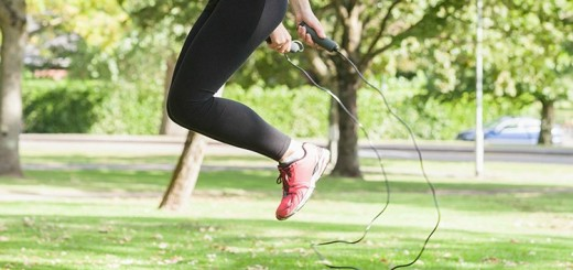 Side view of sporty woman skipping in a park